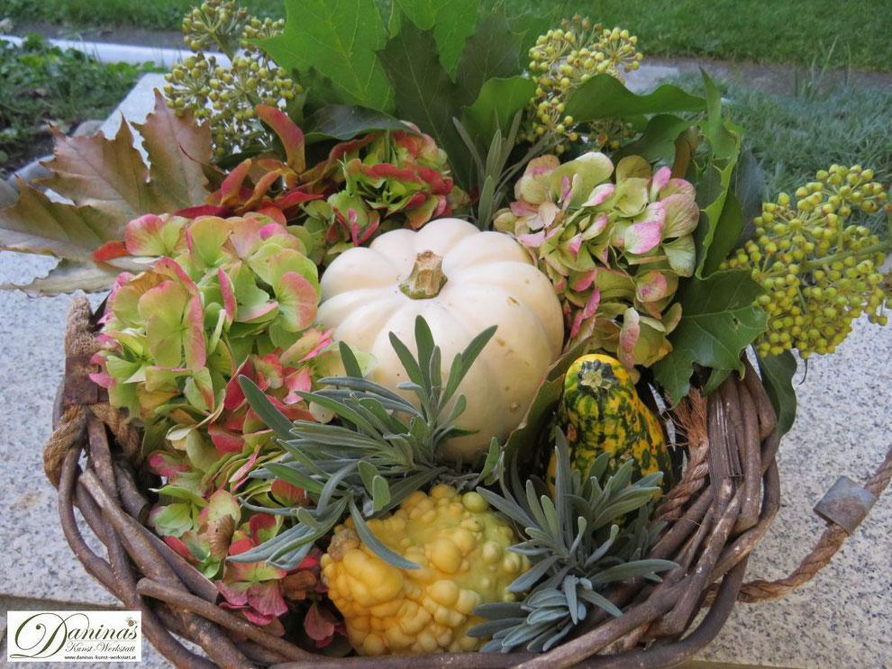 Herbstdeko für den Garten: Weidenkorb mit Kürbissen, Hortensienblüten, Ahornsamen, Lavendel, Efeu und bunten Blättern