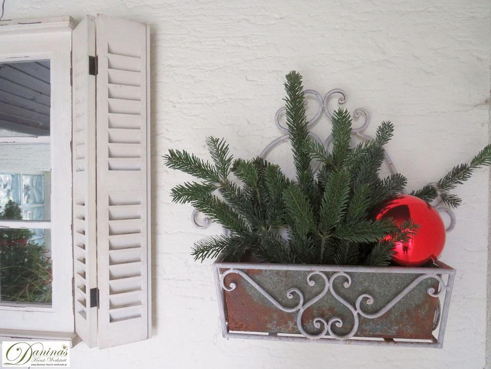 Weihnachtsdeko mit Tannenzweigen und roter Dekokugel für die Terrasse
