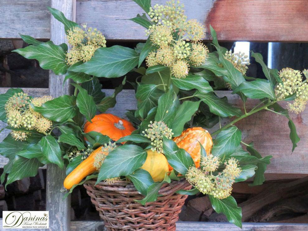 Herbstdeko für draussen: Rattan Füllhorn mit Efeu, orangen und gelben Kürbissen