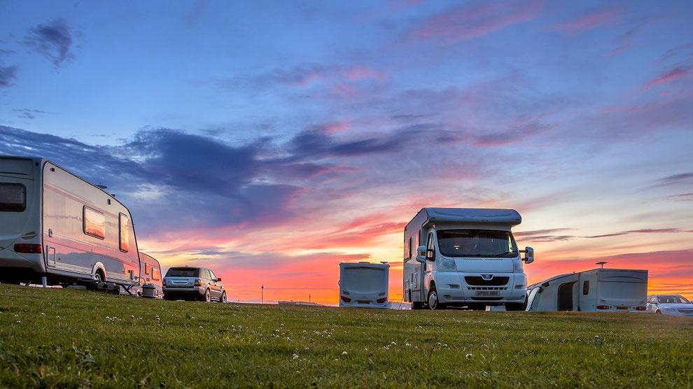 Mehrere Wohnwagen und Wohnmobile stehen in der Abendsonne beim Sonnenuntergang auf der Wiese. Hoffentlich alle gut CDW-Versichert mit der ERGO Womo Reiseschutz-Versicherung