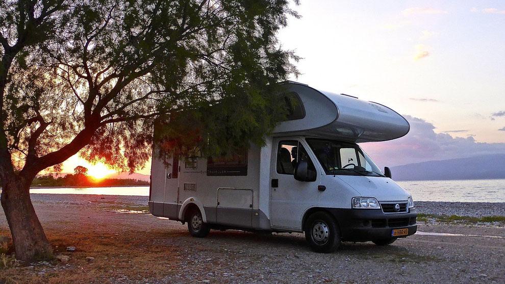 Ein Wohnmobil am Strand im Sonnenuntergang. Caravaning-Urlaub boomt in der Corona-Zeit. Gut geschützt mit einer Camping-Reiseversicherung und CDW-Versicherung der ERGO.