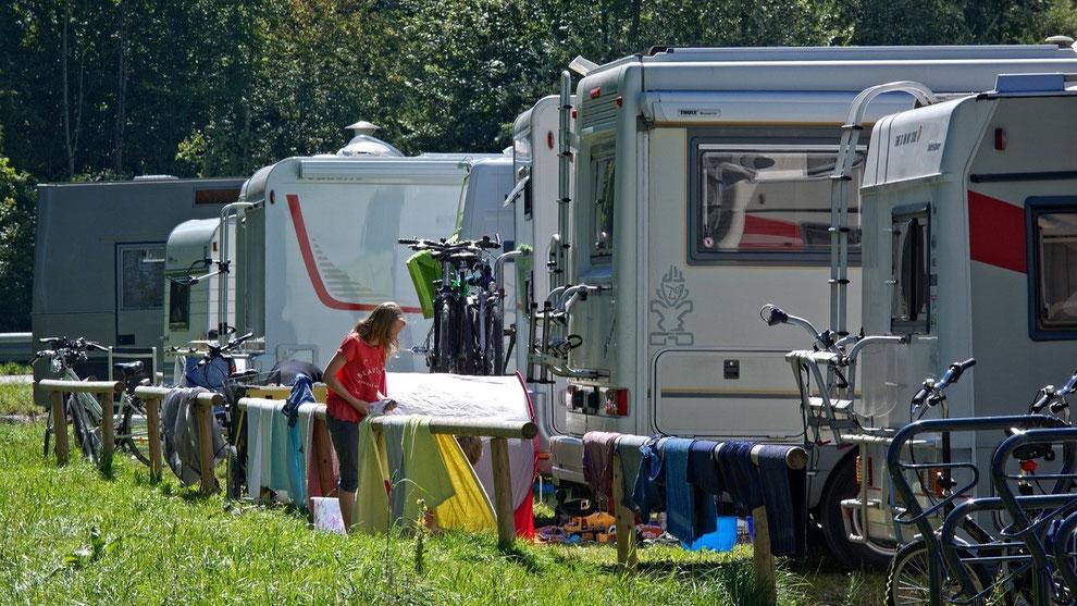 Mehrere Wohnmobile auf einem Campingplatz. Eine Frau hängt Wäsche auf. Camping-Urlaub boomt in der Corona-Zeit. Gut geschützt mit einer Camping-Reiseversicherung und CDW-Versicherung der ERGO.