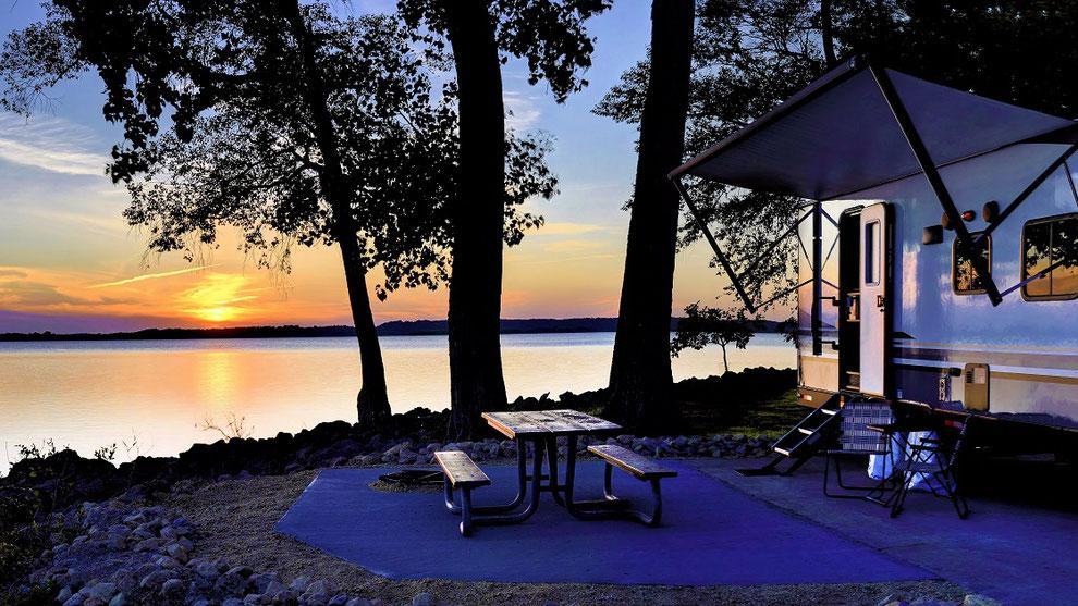 Camper Wohnmobil steht am See beim Sonnenuntergang an einem See. Gut für Camping Caravaning Urlaub ist die CDW-Versicherung der ERGO. Extra für Camper mit Womo Reiseschutz und Inhaltsversicherung mit Sportgeräte-Versicherung