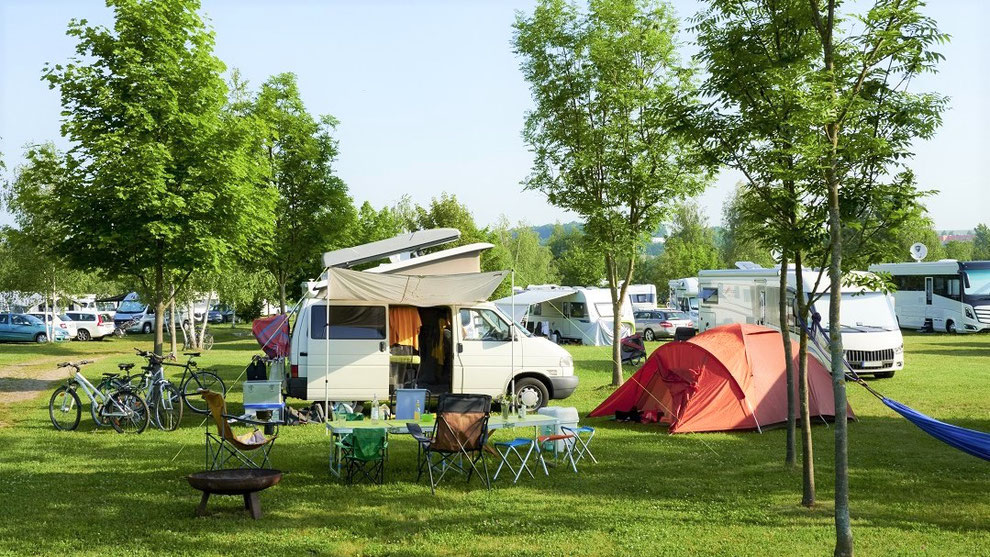 Mehrere Wohnwagen und Wohnmobile stehen auf einem Campingplatz nebst rotem Zelt, Hängematte, Campingstühlen und Fahrrädern. Alle gut Camping versichert. Mit CDW und Camping-Reiserücktritts-Versicherung für Urlaub auf dem Campingplatz.