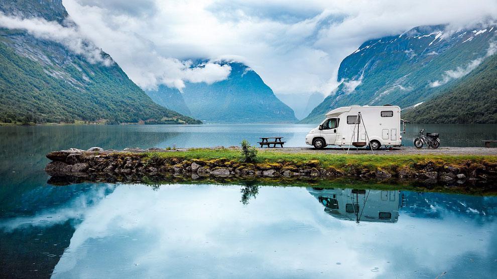 Wohnmobil mit Fahrrädern beim Campingurlaub einsam am See zwischen Bergen mit Nebel und tiefhängenden Wolken. Das Reisemobil spiegelt sich im See.
