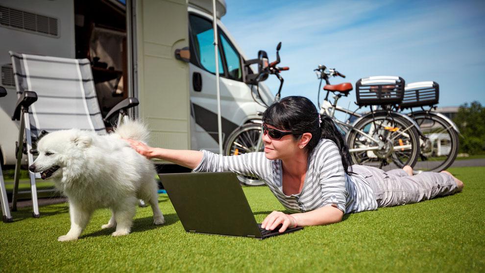 Frau mit schwarzem Haaren liegt mit einem Laptop auf der Wiese und streichelt einen weißen Hund. Im Hintergrund sieht man ein weißes Wohnmobil und zwei Fahrräder.