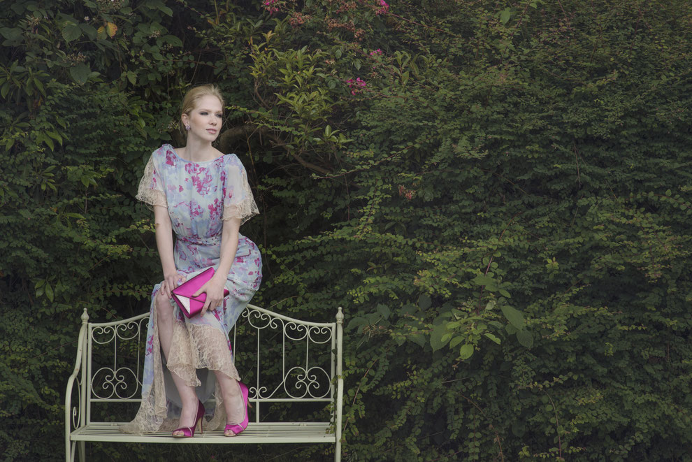 Frau auf Bank sitzend mit Sommerkleid und passend eingefärbten Schuhen und Handtasche