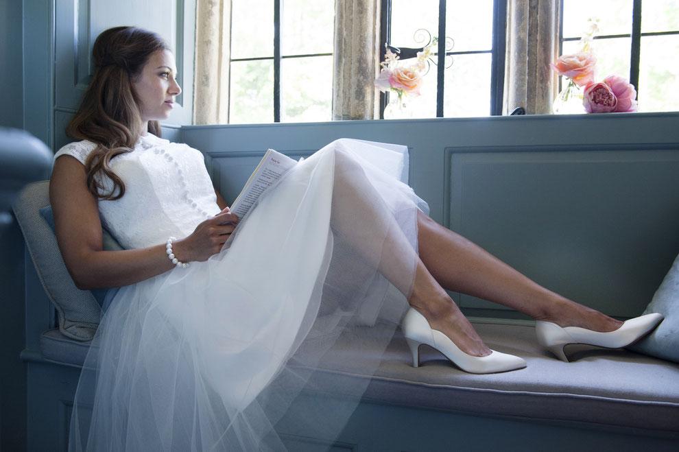 Braut im Brautkleid auf Bank sitzend mit Brautschuhen und Buch