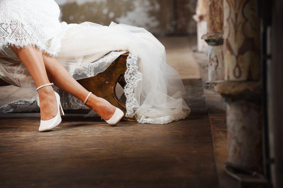 Schuhe, angezogen an Brautfüße, sitzend im Brautkleid mit Schleppe