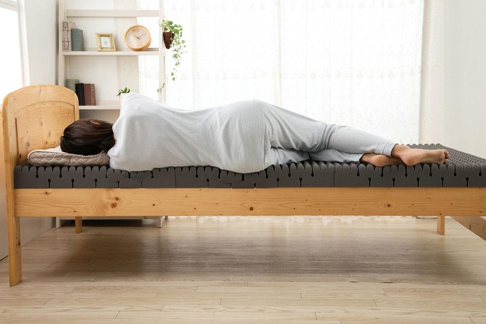 整圧マットレスの写真 女性が横向きに寝ていて整圧マットレスの変化がわかる
