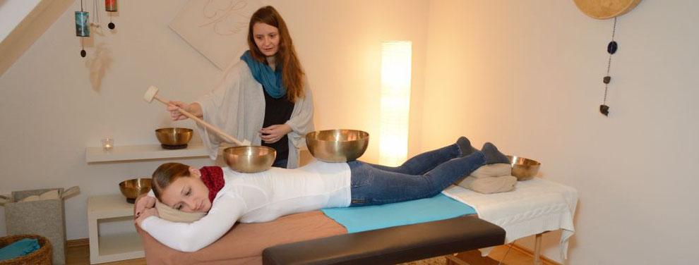 Eine Klientin liegt in Bauchlage auf der Massageliege. Im Schulterblätterbereich steht die Herzschale, auf dem Gesäß eine  Beckenschale und an den Füßen steht eine weitere Beckenschale. Die Klangpädagogin klingt gerade die Herzschale an.