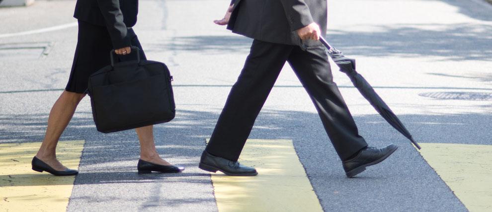 Un monsieur âgé et une femme âgés traversent la route