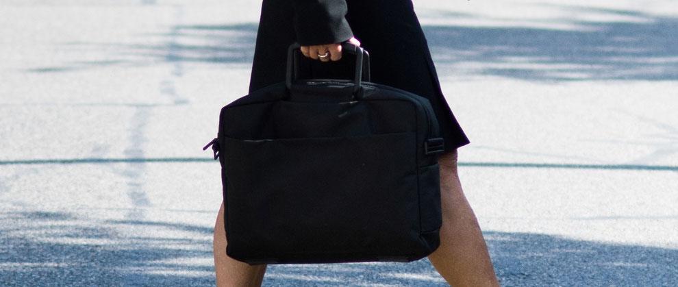 Auf der Strasse mit Aktentasche in der Hand