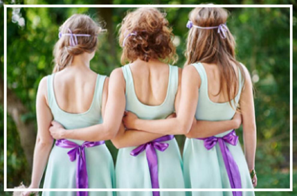 drei Mädchen in gleichen pastellfarbigen Brautjungfernkleidern