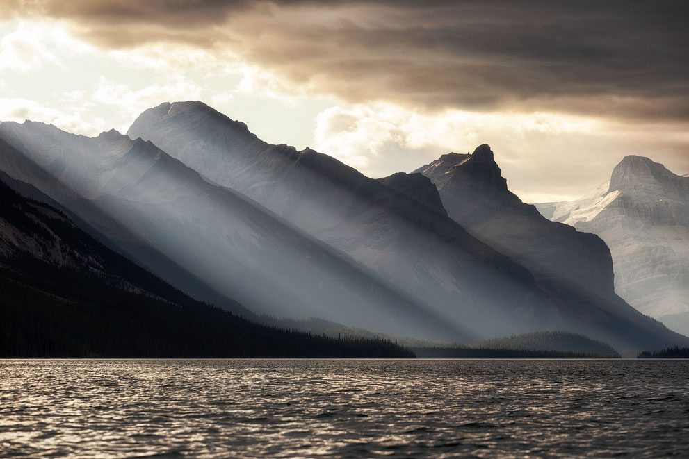 Sun rays hitting the mountains around Maligne Lake. guide to multi day kayaking trip to Spirit Island and Coronet Creek on Maligne lake