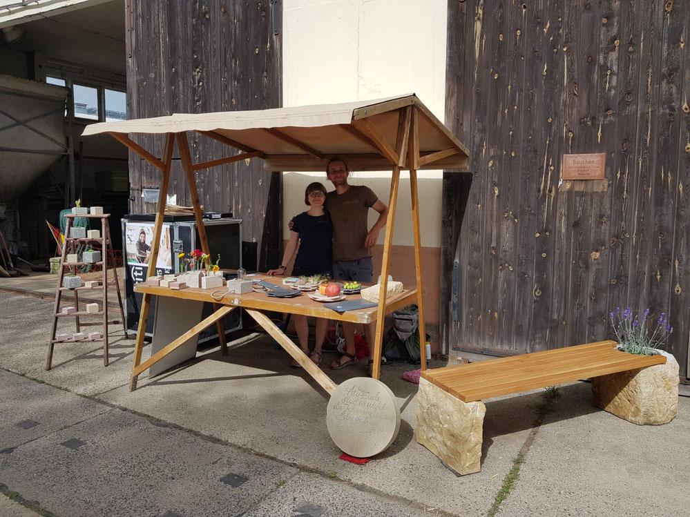 Anne Fischer und Marcus Scheffczyk von Meilenstein stehen an ihrem Stand bei einem Naturmarkt