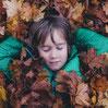 Een kind dat buiten op de grond ligt met herfstbladeren om zich heen