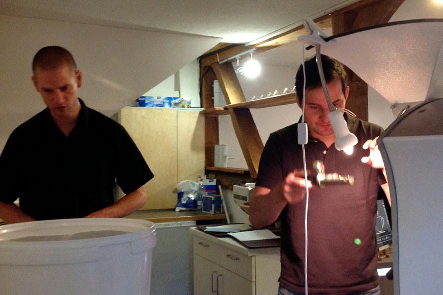 Pingo und Sven beim Rösten. Pingo schreibt das Profil auf bzw. gleicht es ab, Sven behält die Bohnen im Auge.