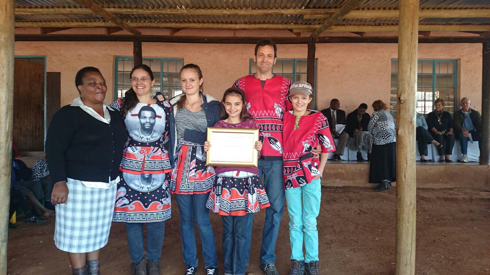 Diplom und traditionelle Kleidung als Dankeschön