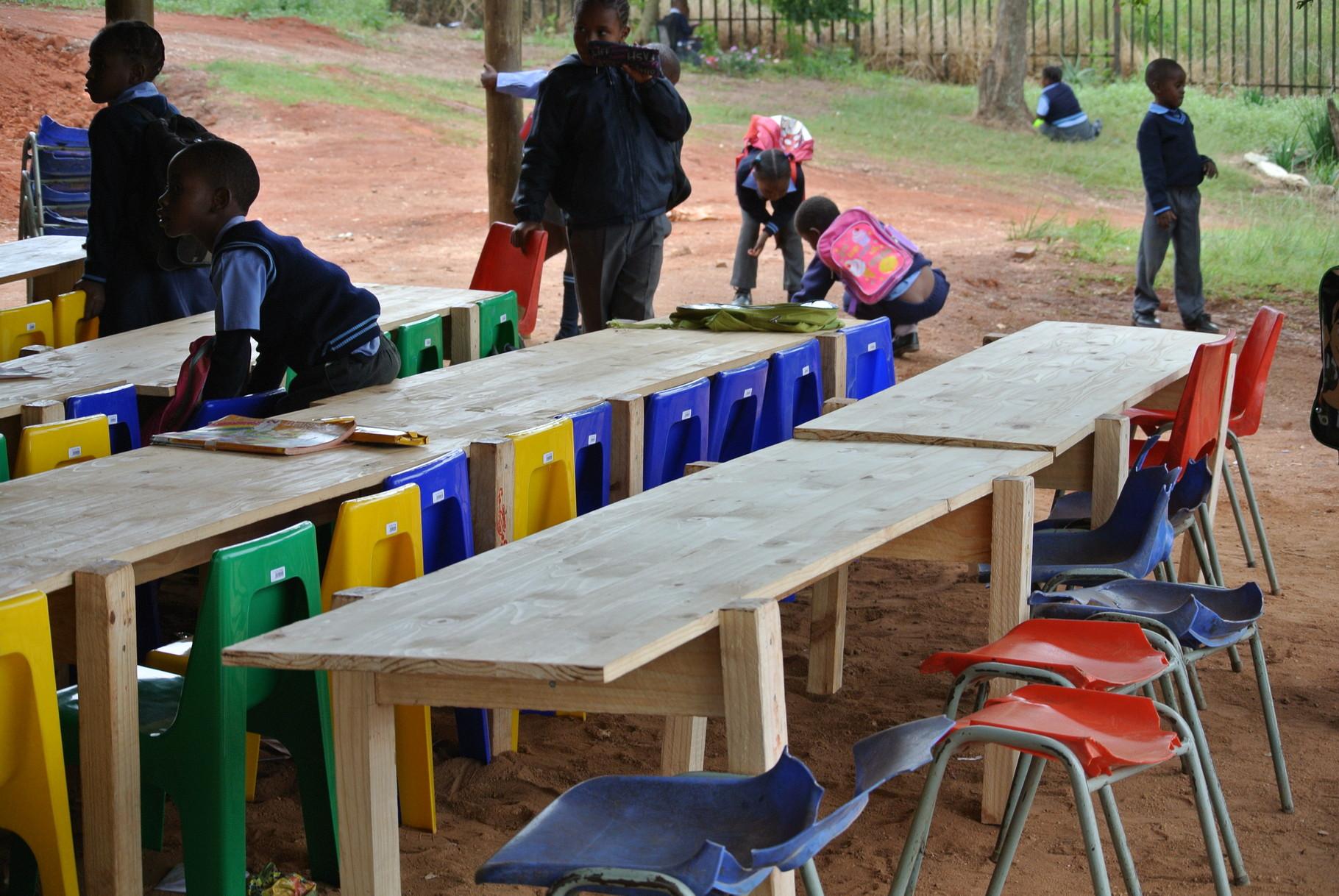 Tische und Stühle für die Klasse unter dem Unterstand