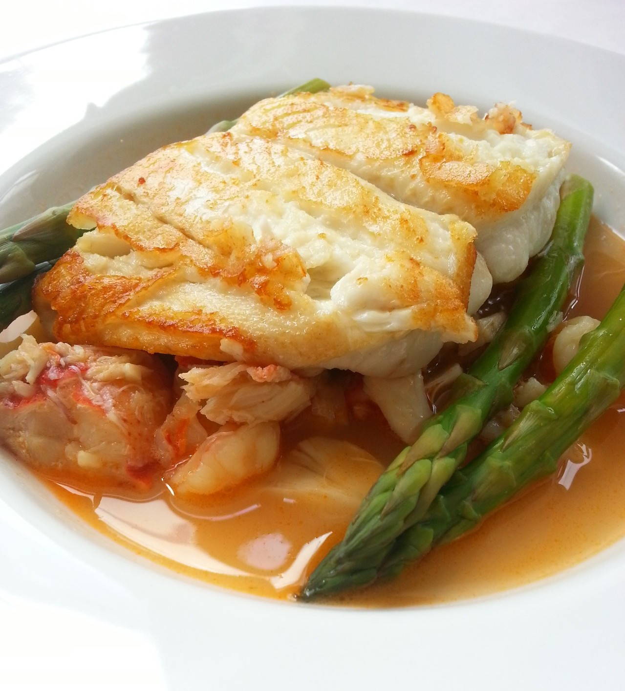 Pan Roasted Golden Bass with Lobster, Lump Crab Meat and Shrimp &n Seafood Au Jus