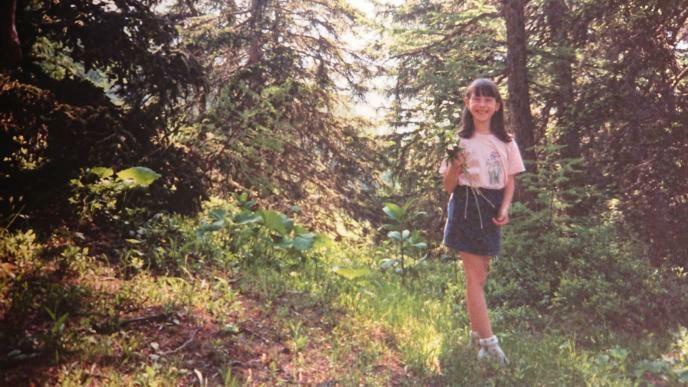 Elisa da bambina mentre raccoglie le piante.