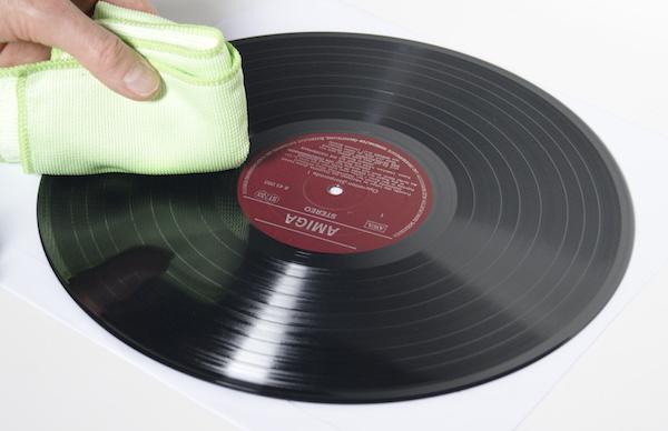 Mit einem grünen Mikrofasertuch wird eine nasse Schallplatte abgewischt