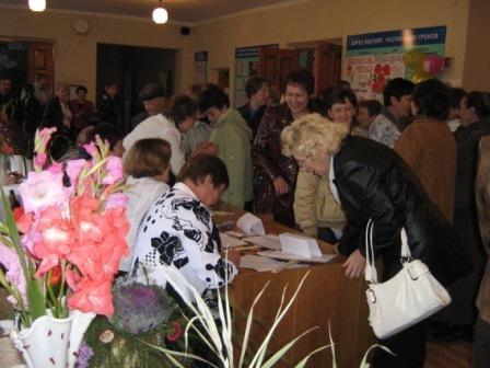 В фойе школы идет регистрация гостей по годам выпуска.