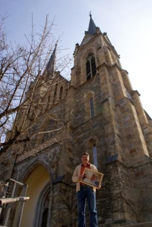 Jounalist Winfried Gburek mit einem Foto der Ausstellung vor dem Pongauer-Dom in St. Johann im Pongau, einem Ausstellungsort der Foto-Reportage