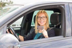 Frau im Auto mit Führerschein