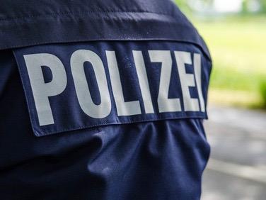Hier sieht man die Polizeiaufschrift auf dem Rücken der Einsatzkleidung eines Polizisten