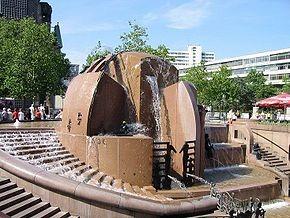 Weltkugelbrunnen vom Joachim Schmettau. Rechts vorn im Wasserbecken, zwischen den roten Granitblöcken das Motiv Menschengitter.[1]