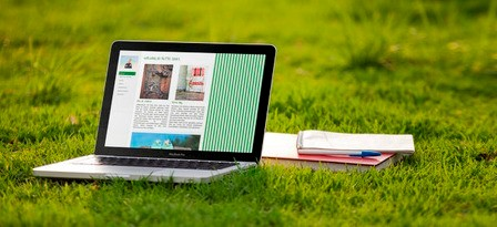 Laptop und Notizbuch auf Wiese