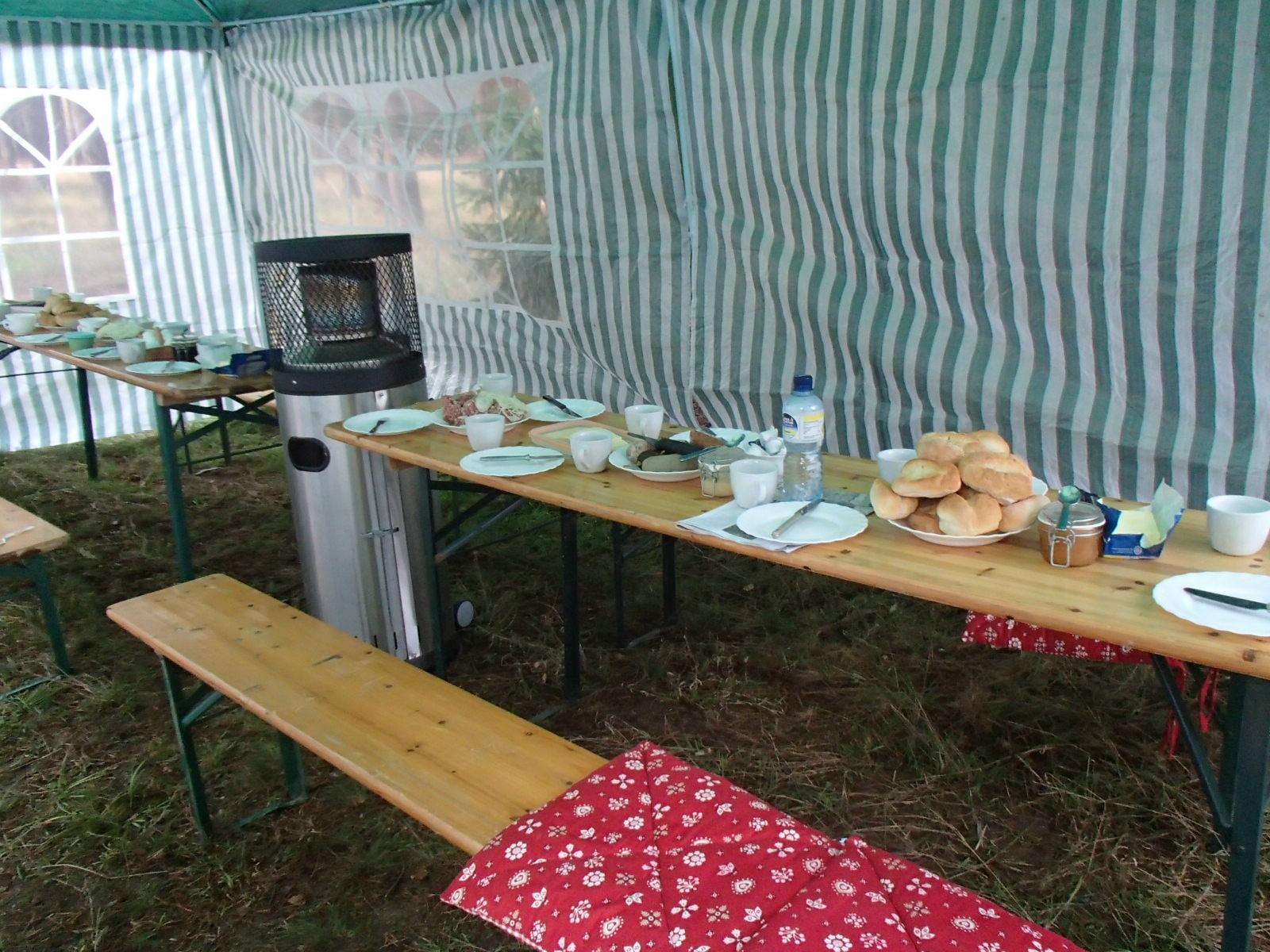 Im Zelt wird schon der Frühstückstisch gedeckt.