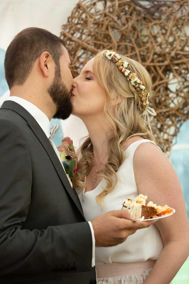 Hochzeitslocation Heidersbacher-Mühle 1, 74834 Elztal, Hochzeitsfotograf, Hochzeitsbilder, Hochzeitsreportage, Hochzeitskuss junges Brautpaar nach dem ersten Stück Hochzeitstorte