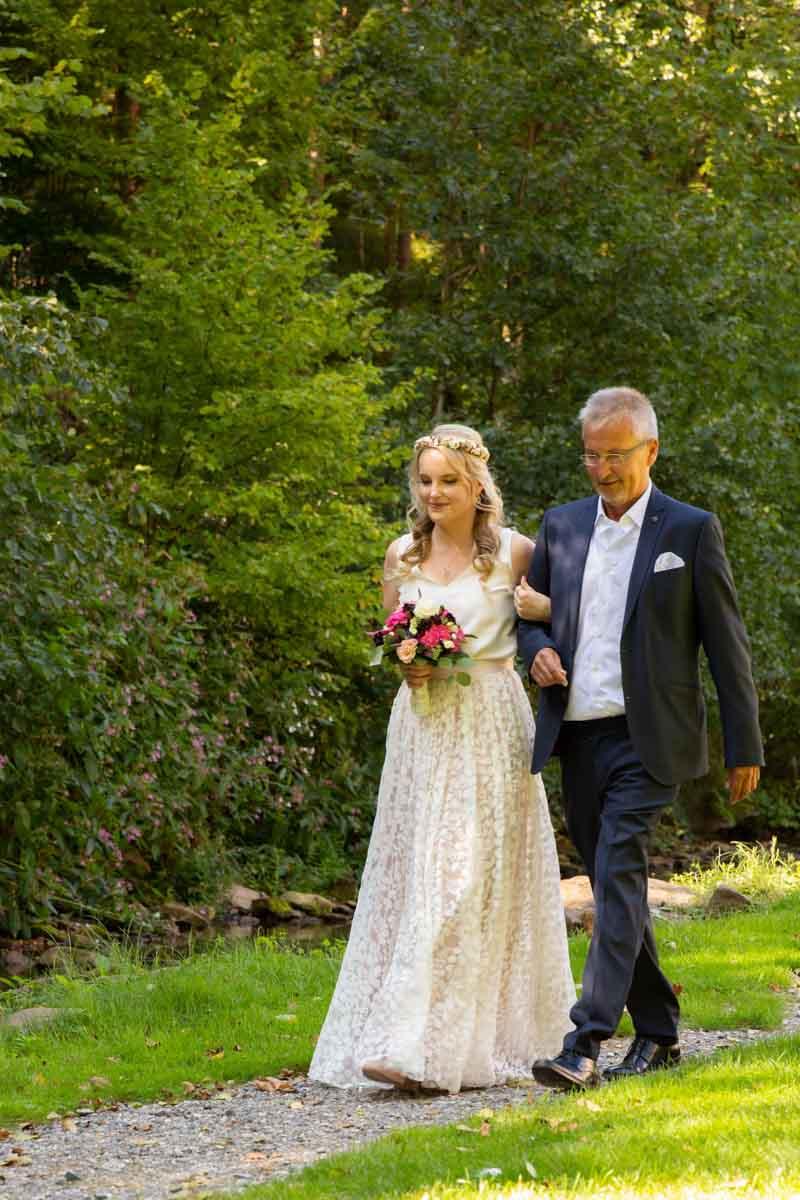 Hochzeitslocation Heidersbacher-Mühle 1, 74834 Elztal, Hochzeitsfotograf, Hochzeitsbilder, Hochzeitsreportage, Vater begleitet seine Tochter zur Trauung, Braut und Brautvater auf dem Weg zur Trauung