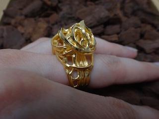 Un gros plan sur une main posée sur du bois. Elle porte une grosse bague dorée. Son design se compose de boucles et de spirales.