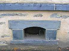 4 blocs de schiste taillé : de haut en bas, le bandeau, le linteau, les claveau et l'appui