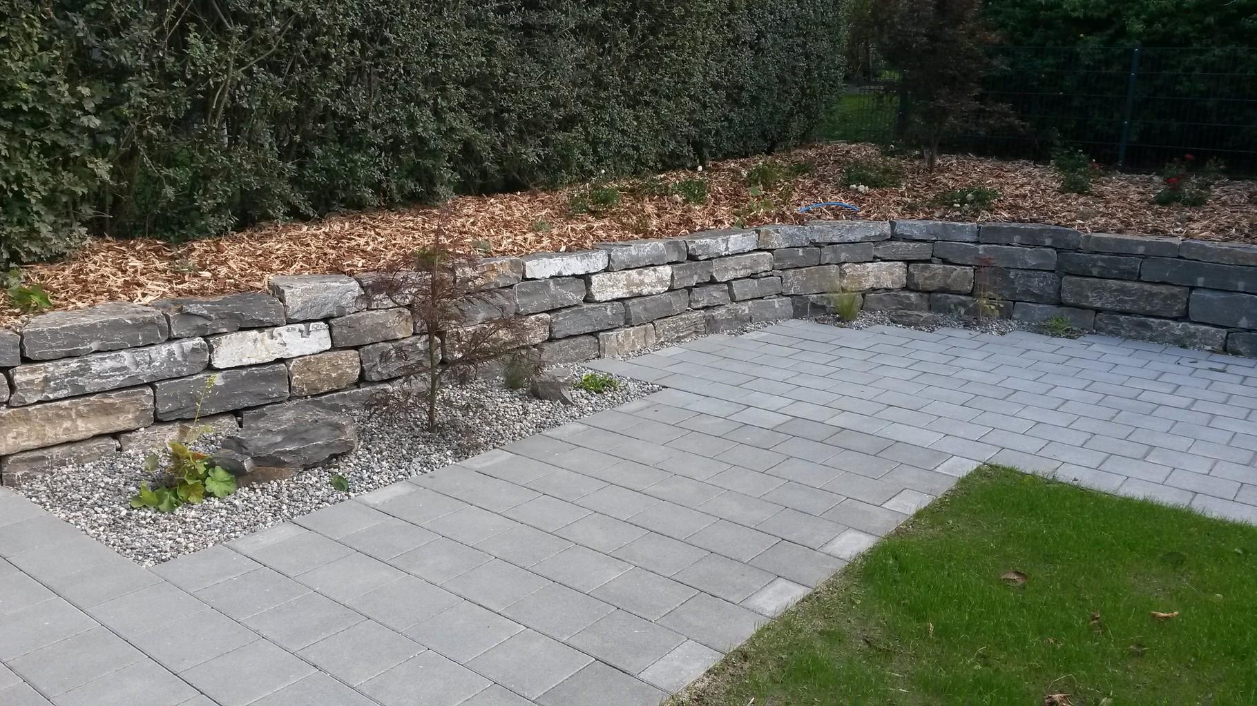 Sitzplatz mit Natursteinmauer und Bepflanzungen
