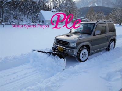 スノープラウを摂り付けた自動車を使用した除雪のようす