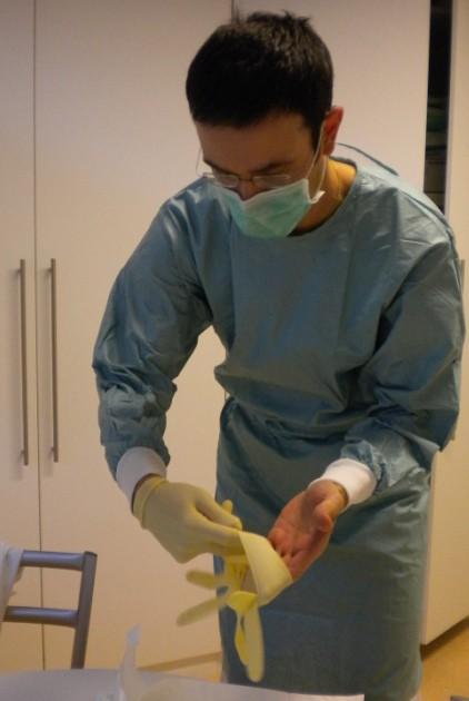 Vorsichtiges Anziehen der sterilen chirurgischen Handschuhe