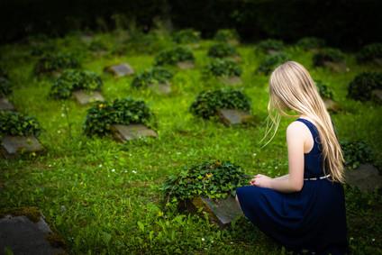 Enkelin am Grab ihres Großvaters