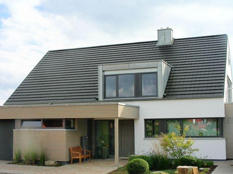 Wohnhaus mit ebenen Tonziegeln Gauben mit Stehfalz aus Titanzink