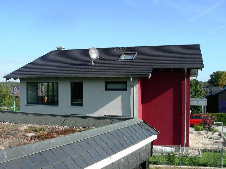 Modernes Wohnhaus mit ebener Tonziegeleindeckung und Titanzinkarbeiten an Carport