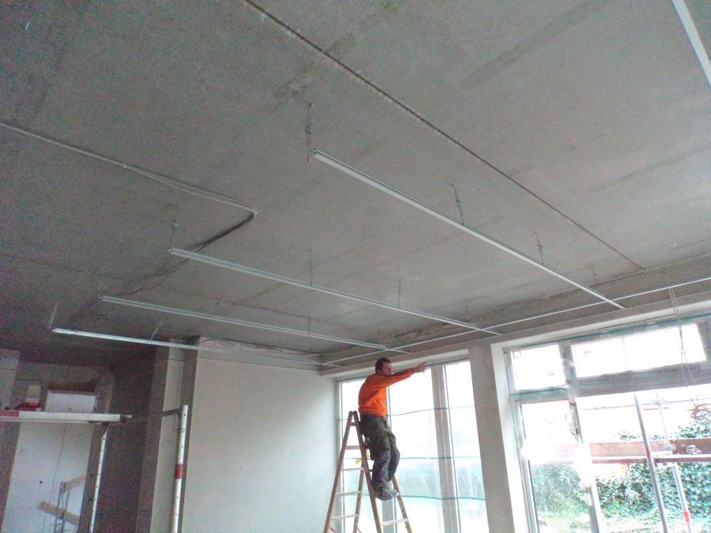 (24.11.2015) EG Mietbereich Sanitätshaus: Die Unterkonstruktion für die abgehängte Decke wird eingebaut. Die Fensterfassade ist geschlossen.