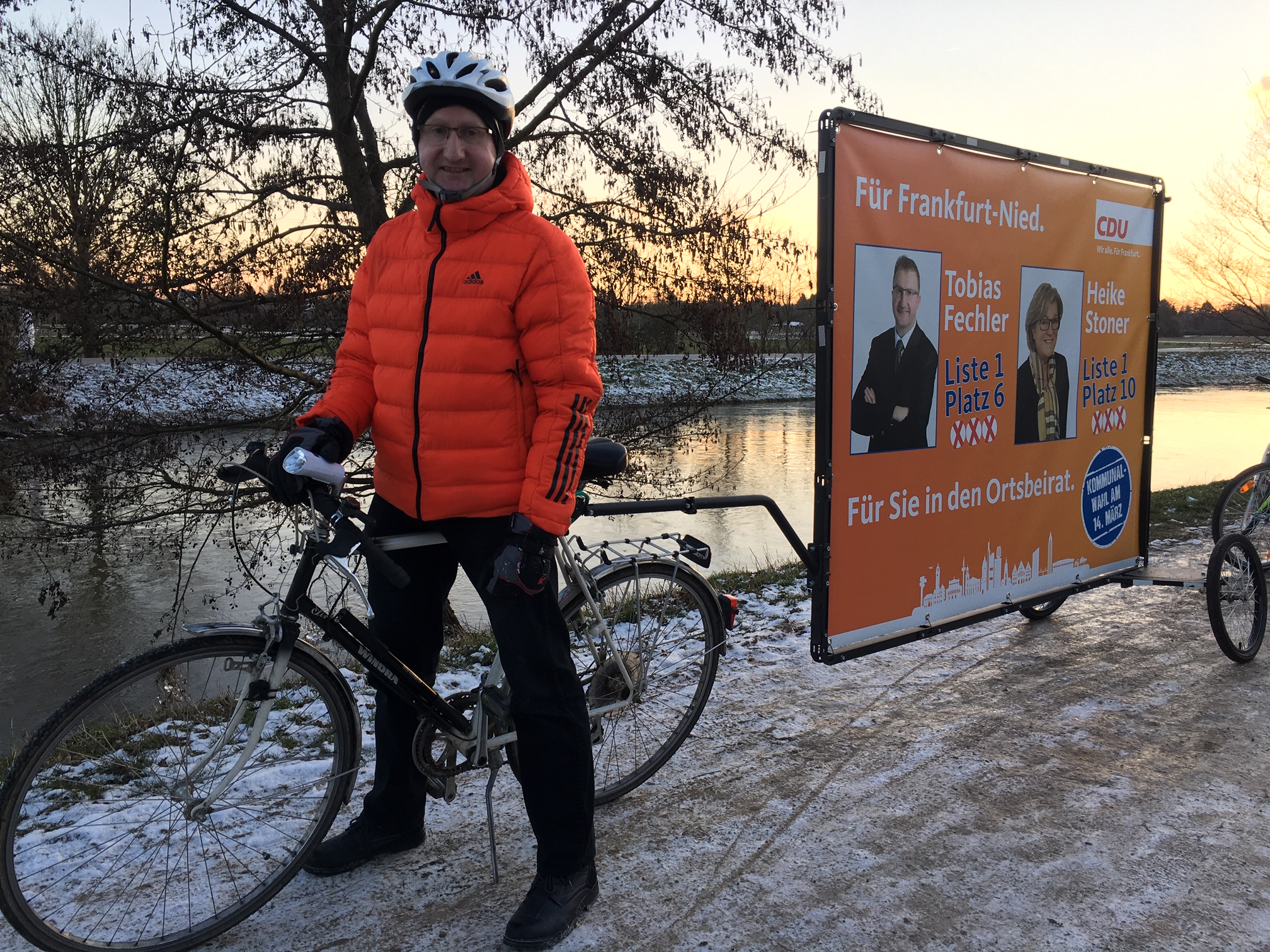 Tobias Fechler mit Werbebanner unterwegs an der Nidda.