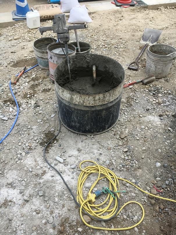 セメントと骨材と水を、電動かくはん機で混ぜています