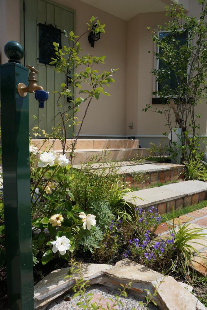 古レンガや天然石を用いた階段回り。花と素材の組み合わせも素敵に出来た。
