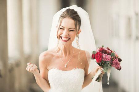 Brautfrisuren für die Hochzeit: Eine überglückliche Braut mit Schleier und Hochsteckfrisur in schulterlosem Brautkleid hält einen Brautstrauß aus rosa- und rotfarbenen Blumen.