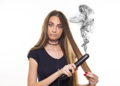 Eine junge brünette Frau glättet sich eine Haarsträhne mit einem Glätteisen, während aus diesem eine Rauchsäule aufsteigt.